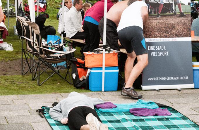 """Ein Teilnemer liegt auf einer Decke und ruht sich aus. Im Hintergrund ein Schild mit der Aufschrift """" Eine Stadt. Viel Sport. """""""