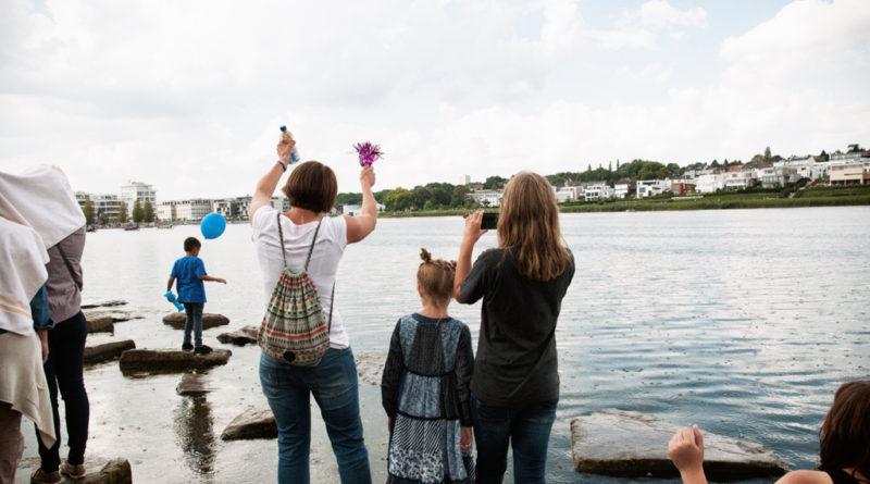 Das Publickum steht auf am Rand des Sees liegende grosse Steine. Und feuern mit Wedel und Rassel an.