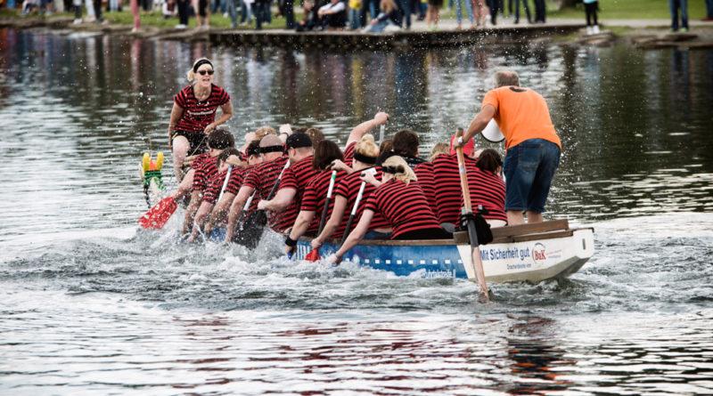 Das Drachenboot setzt sich in Bewegung. Der Steuermann und der Trommler schreit und feuern die Mannschaft an.